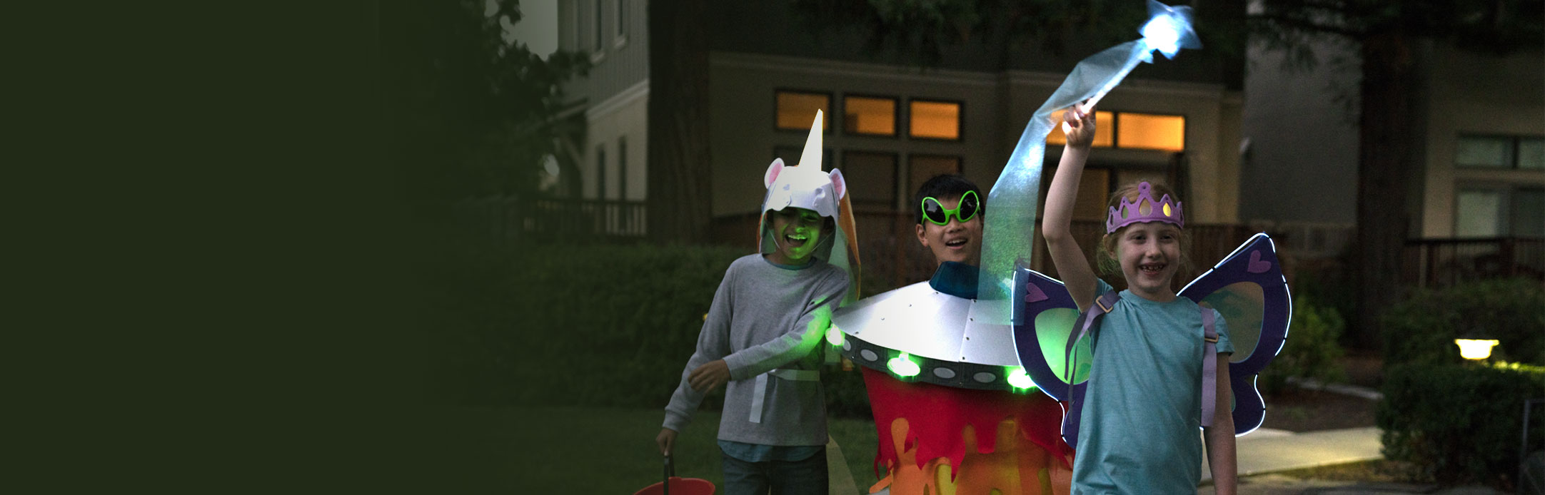 Kids walking on the street in KiwiCo's do-it-yourself Halloween costumes as a dinosaur, unicorn, UFO, and light-up wings.